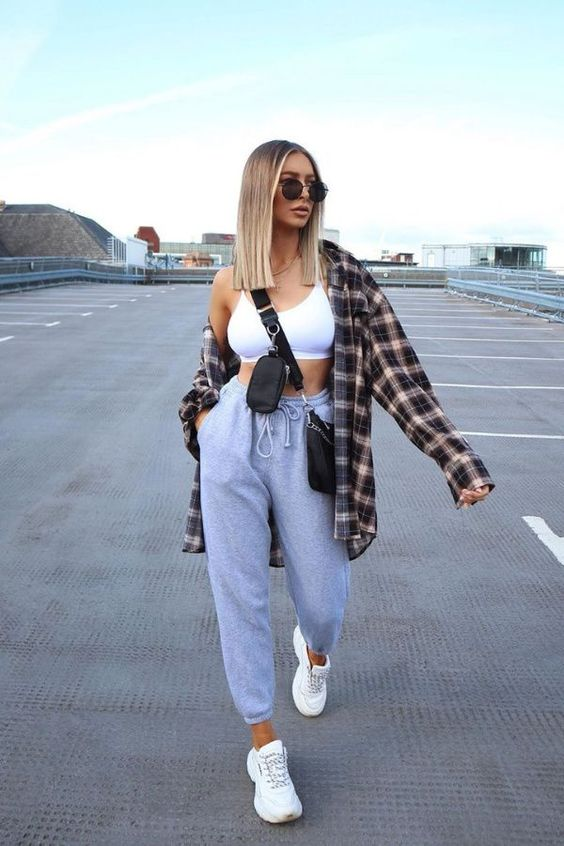 a sport chic outfit with a white crop top, grey sweatpants, white trainers, a plaid shirt and a black bag