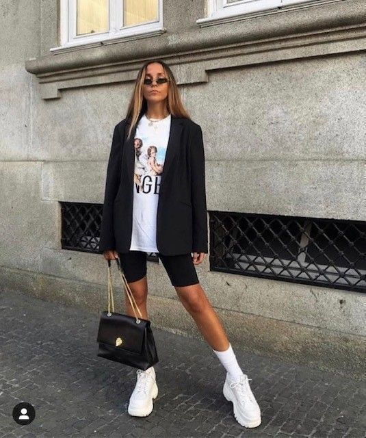 a sporty look with a printed tee, black biker shorts, a black oversized blazer, white socks and trainers and a black bag