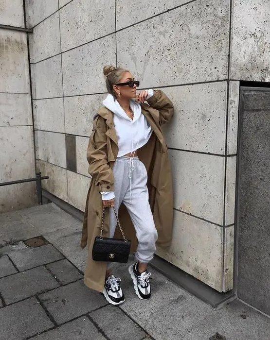 a sporty outfit with a cropped hoodie, joggers, two tone trainers, a camel trench and a black bag