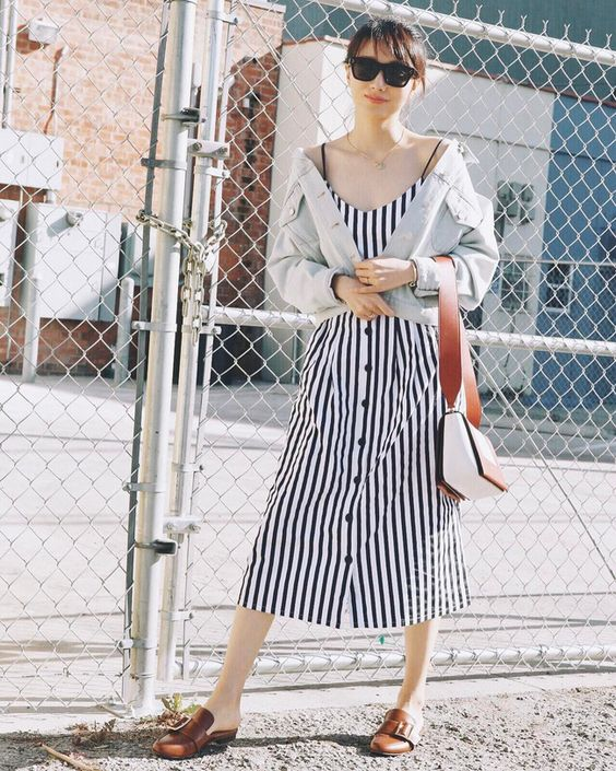 a striped navy and white linen midi sundress, brown mules, a distressed cropped denim jacket and a two tone bag