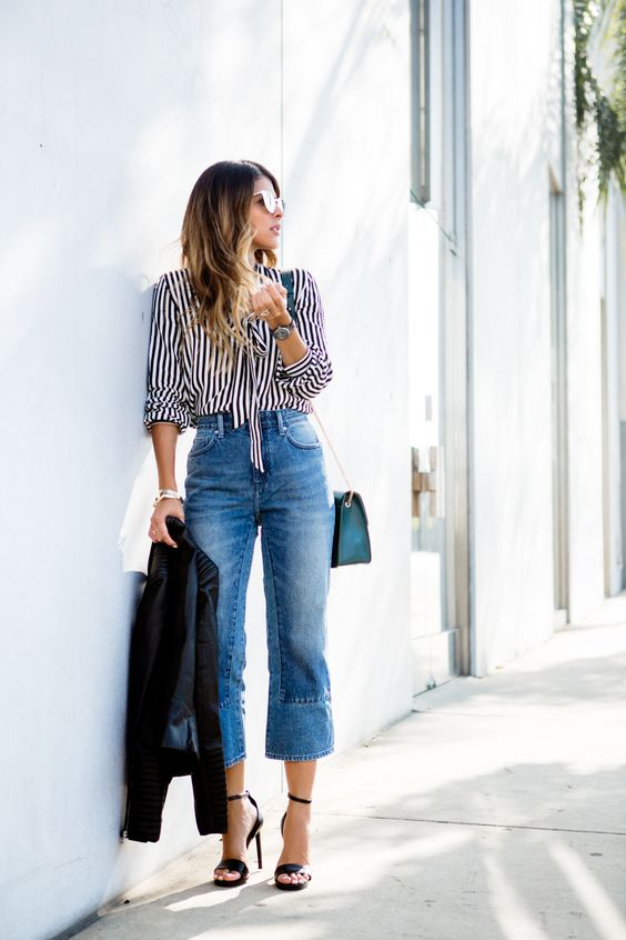 a striped shirt, blue cropped flare jeans, high heels, a blue bag and a black jacket