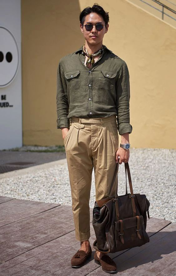 a stylish linen outfit with a green shirt, tan trousers, a brown bag and moccasins plus a neck tie