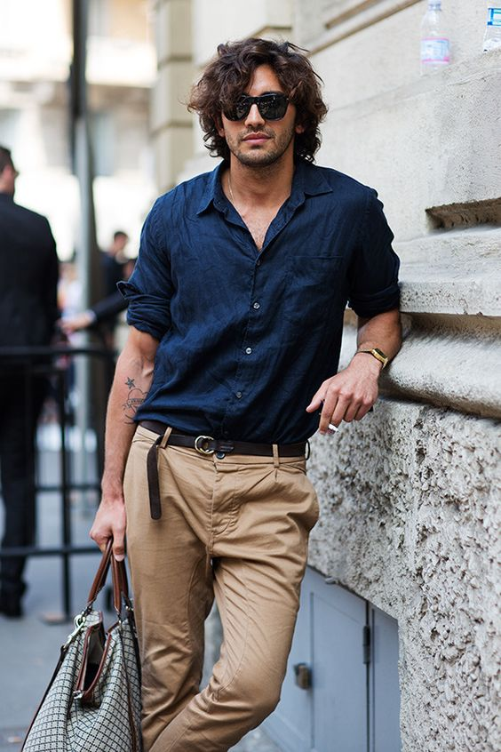 a stylish summer look with a navy linen shirt, tan pants, a black belt and a printed bag is a cool idea