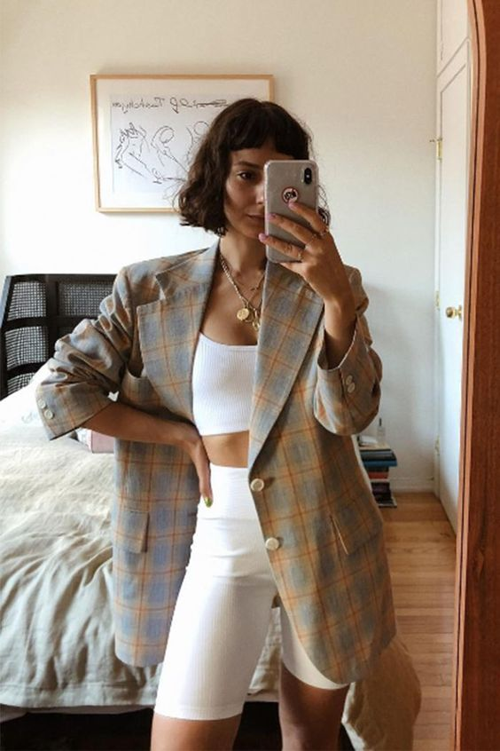 a summer to fall outfit with a white crop top, biker shorts, a plaid grey and yellow blazer plus layered necklaces