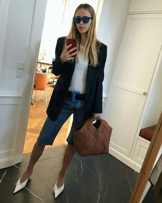 a summer work look with a white tee, blue denim biker shorts, white heeled mules, a woven bag and an oversized black blazer