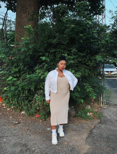 a tan midi dress with a slit, a white denim jacket, white socks and trainers for a summer to fall look