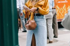 a trendy summer outfit with a mustard off the shoulder crop top, a blue denim midi with a front slit, white mules and a brown bag