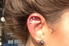 a triple hexlix piercing done with matching stud earrings plus a double lobe piercing done with studs, too