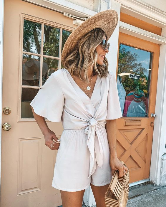 a two piece set with a tied up draped blouse with a deep V neckline and high waisted shorts, a wooden bag and a straw bag for a vacation