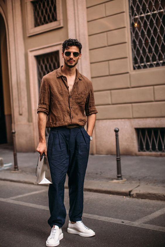 a very relaxed look with a brown linen shirt, navy linen pants, white sneakers is a cool idea to rock on a hot day
