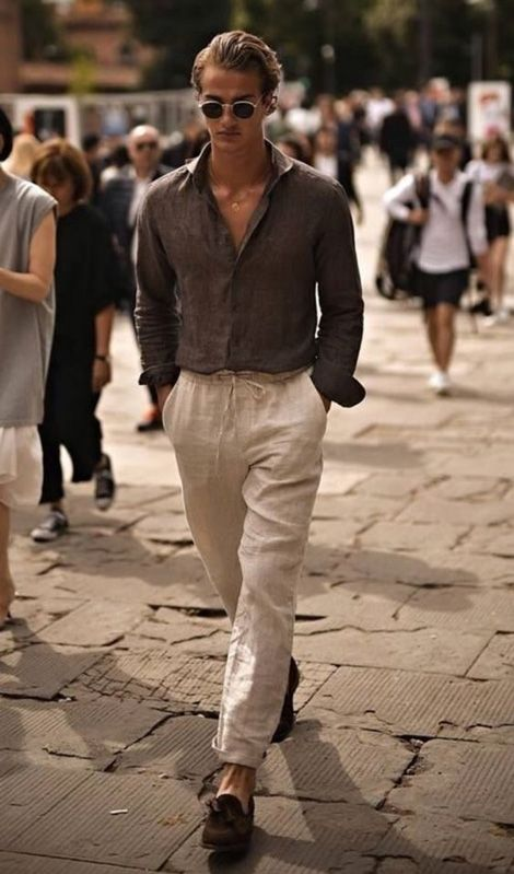 a very relaxed outfit with a grey linen shirt and neutral linen pants, brown moccasins and chic sunglasses