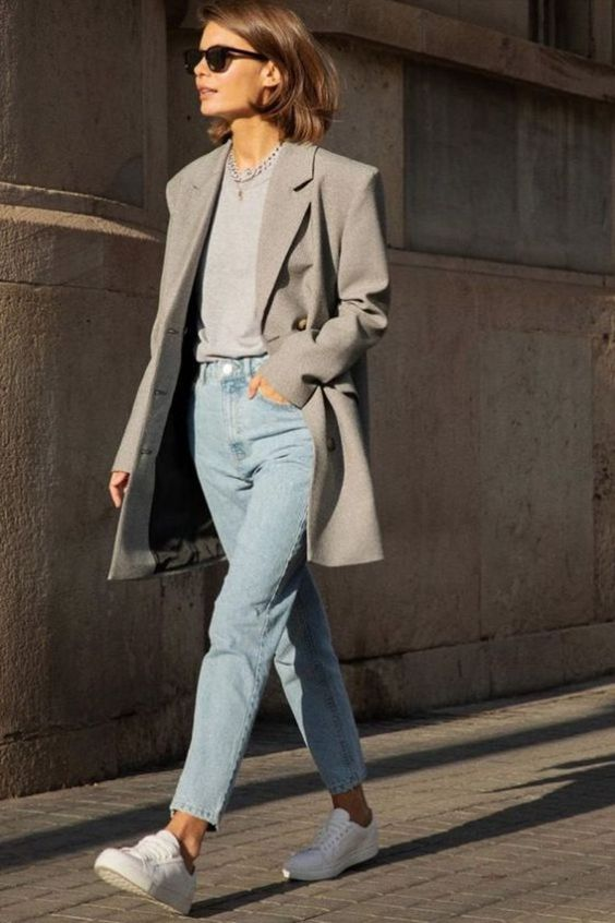 a very simple and comfy casual work outfit with a grey tee, an oversized grey blazer, blue jeans, white sneakers
