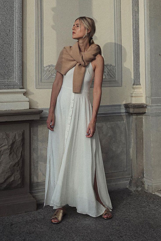 a white A-line maxi dress with buttons and slits, metallic sliders and a tan sweater for colder weather