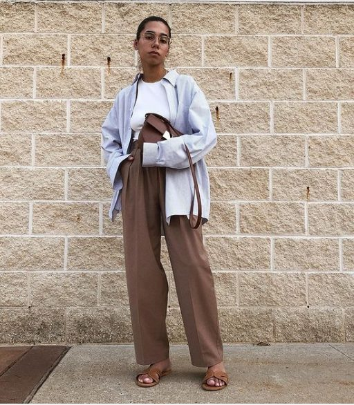a white halter neckline top, brown trousers, a pale blue oversized shirt, brown slippers and a bag
