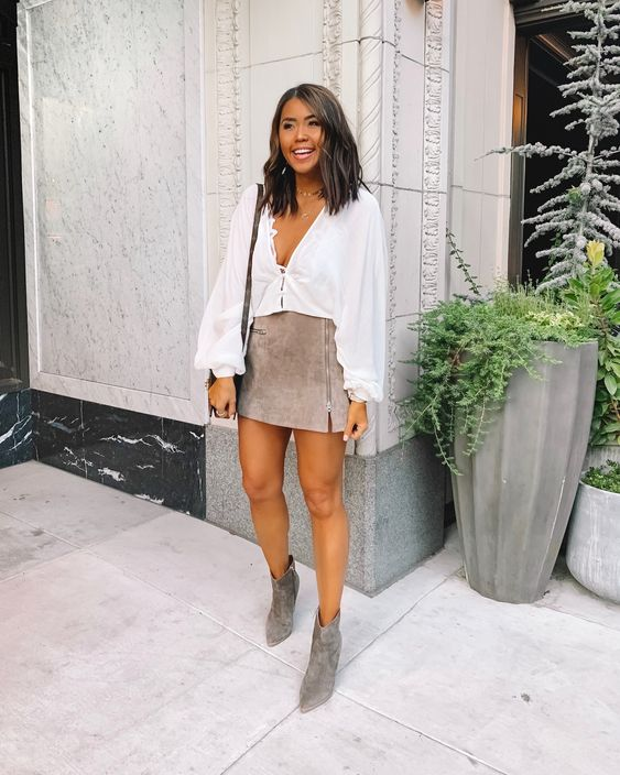 a white linen deep neckline blouse, a grey suede zip midi, grey suede booties, a black bag and layered necklaces