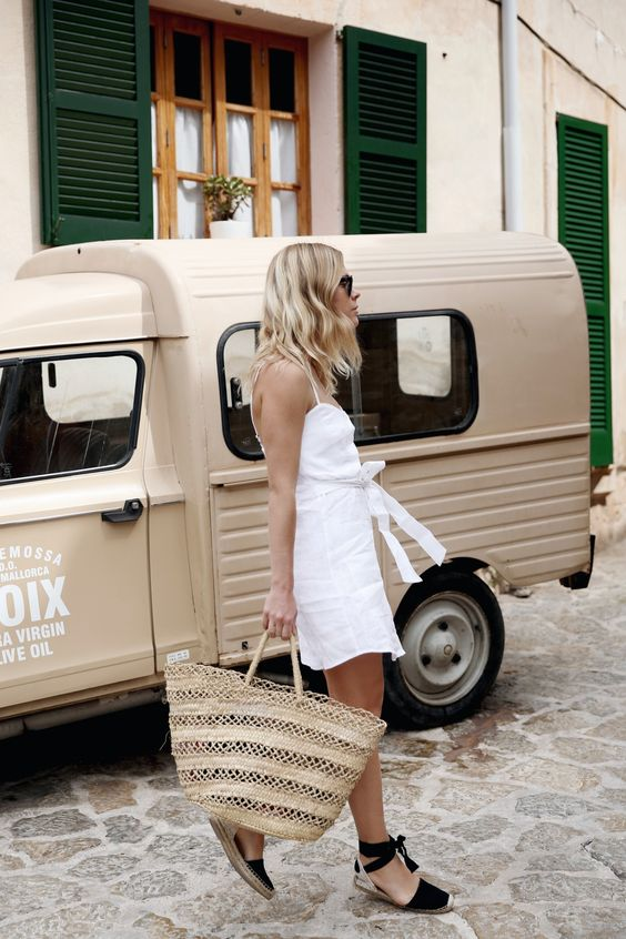 a white linen mini sundress with a sash, black espadrilles, a large woven tote to feel comfy on a hot day
