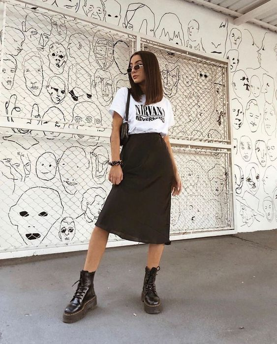 a white printed t-shirt, a black midi skirt, black boots and a black bag for a bold and cool look