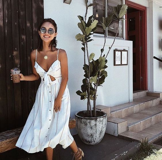a white striped midi linen sundress with a cutout, buttons, a tied up bodice, brown buckle heels and a statement necklace