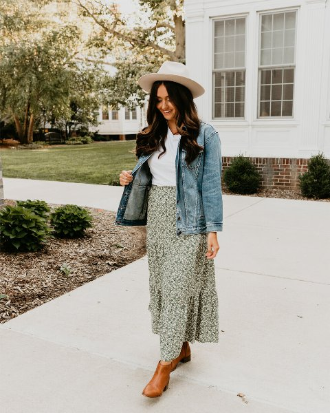 a white t-shirt, a green floral print maxi, amber leather booties, a denim jacket, a hat for a summer to fall look