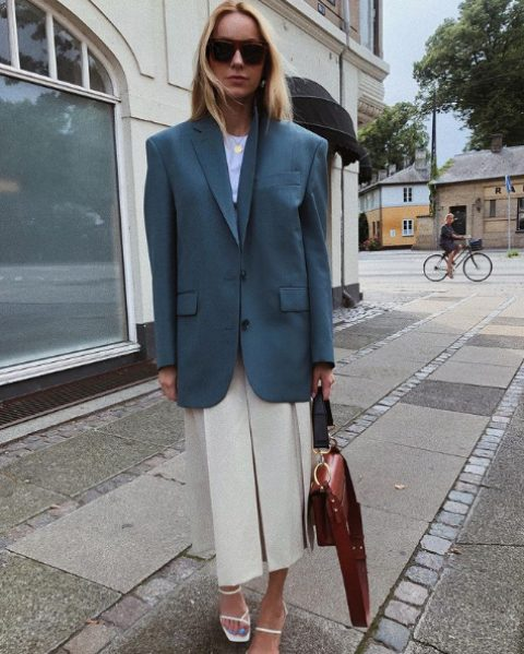 a white t-shirt, a neutral front slit midi skirt, a blue oversized blazer, white square toe heels and a brown bag