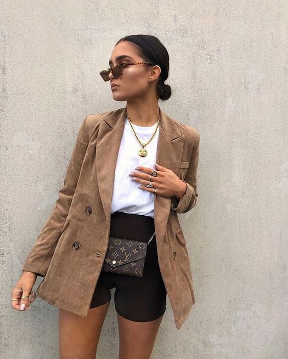 a white tee, black biker shorts, a tan blazer, a waist bag and a statement necklace for a cool look