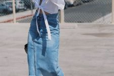 a white tied up crop top, a blue denim asymmetrical midi, black heeled mules and a wooden bag make up a cool outfit for August