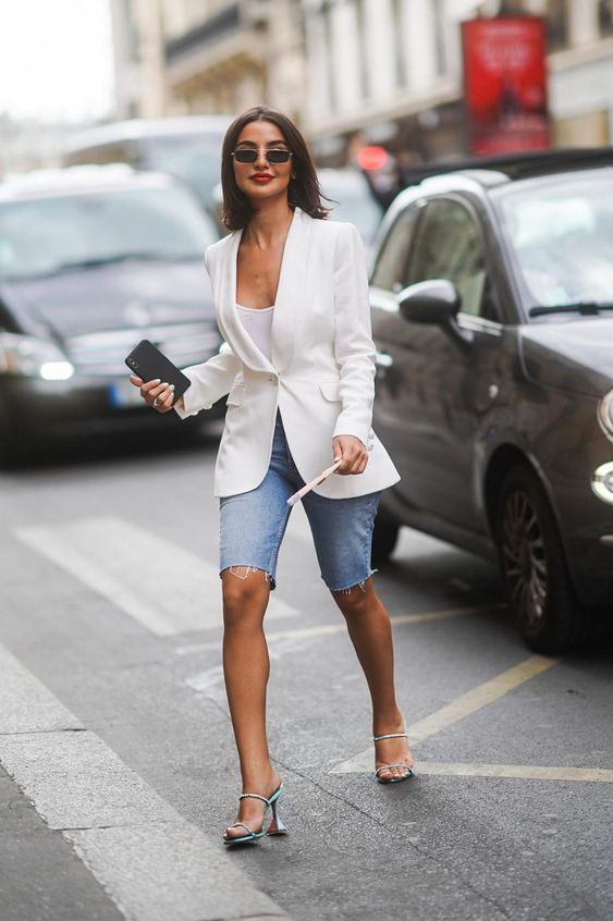 a white top, a fitting white blazer, blue denim biker shorts, turquoise heels for a super chic work look