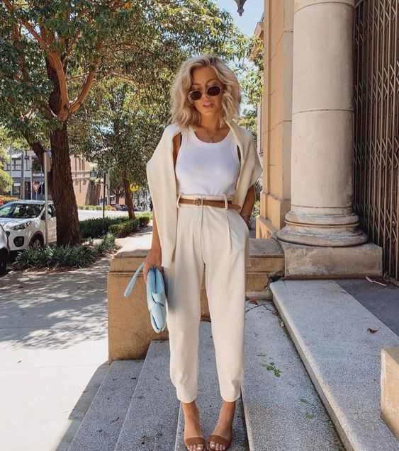 a white top, creamy trousers, a brown belt and heels, a creamy jumper and a blue bag for an effortlessly chic look