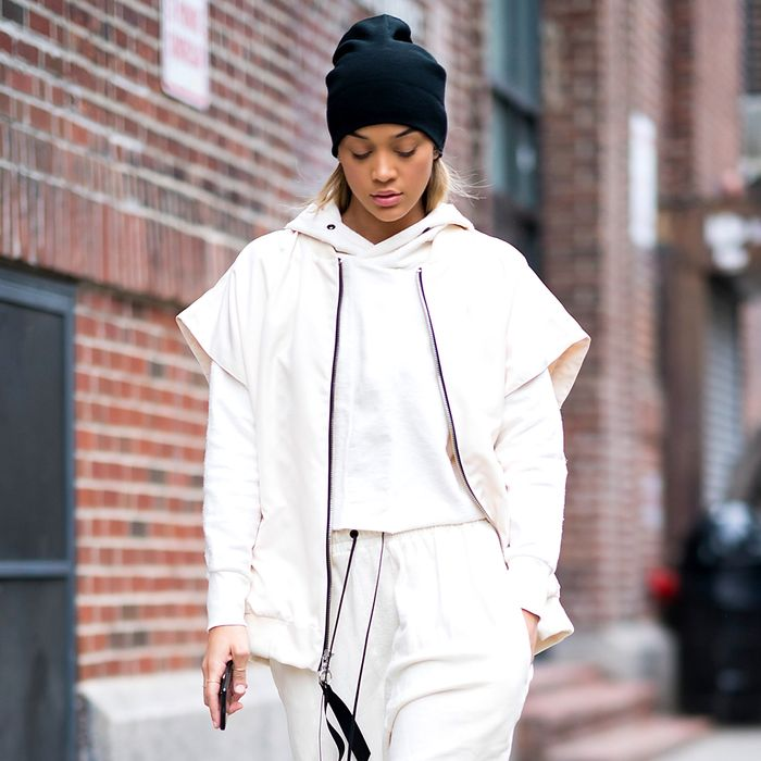 an athleisure inspired look with a white cropped hoodie, sweatpants, a vest, a black beanie