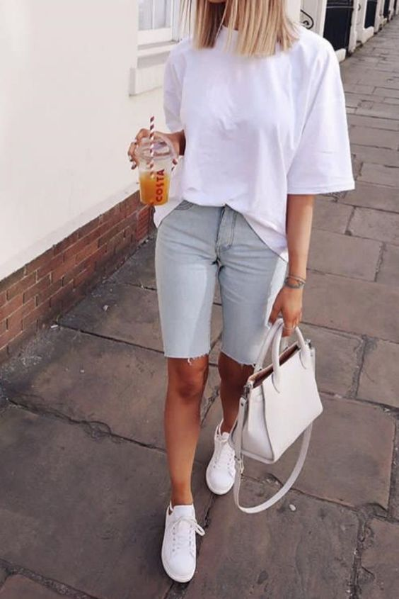 an oversized white tee, distressed blue denim biker shorts, white sneakers and a white bag for a hot summer day