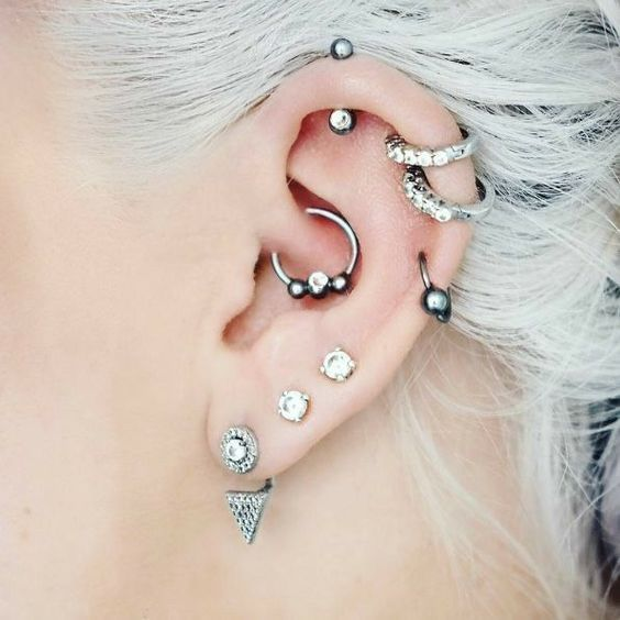 bold ear styling with stacked helix piercings and stacked lobe ones, with a daith piercing all done with cool hoops and studs