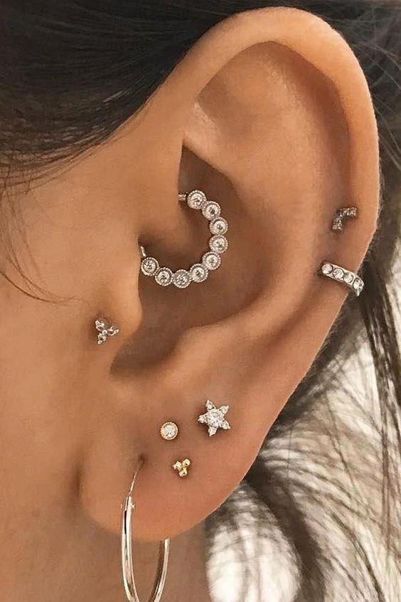 chic and glam ear styling with a stacked lobe piercing, two helix, a tragus and a daith one done with shiny rhinestone studs and hoops