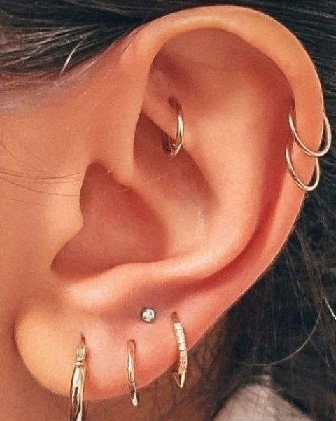 chic ear styling with a stacked lobe piercing, a rook and a double helix one, with hoops and a tiny stud