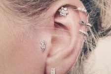 glam ear styling with stacked helix, a lobe, a flat and a tragus piercing done with cool hoops and studs