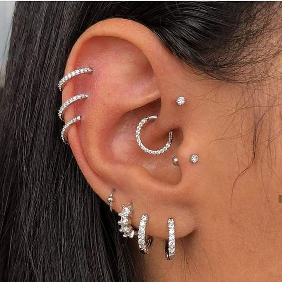 glam ear styling with stacked lobe and helix and flat piercings, a tragus, a forward helix and a daith piercing