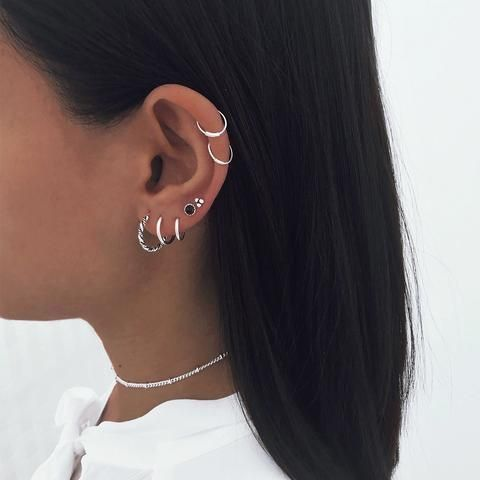 modern ear styling with multiple lobe and a double helix piercing done with chic hoops and studs is wow