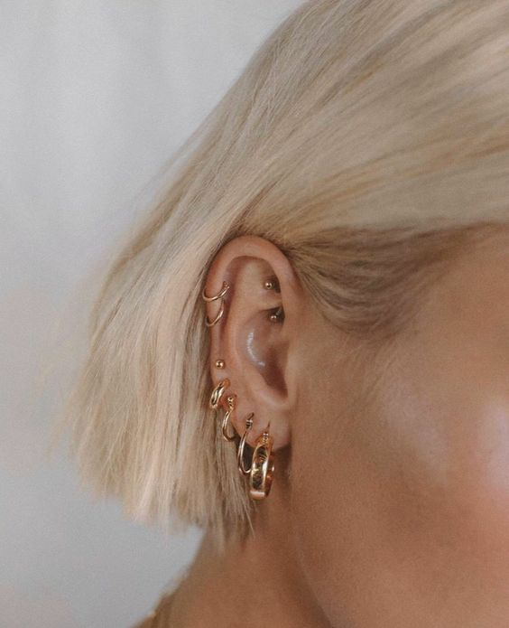 modern ear styling with stacked lobe and helix piercings done with hoops plus a rook piercing for a bolder look