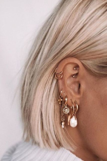 multiple stacked lobe piercings, a double helix piercing and a rook one done with chic gold earrings