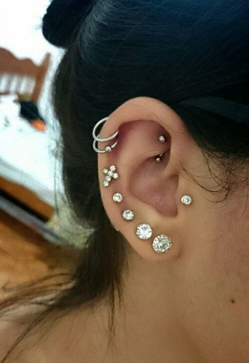 stacked lobe and helix piercings done with stud and hoop earrings plus a tragus and a rook piercing