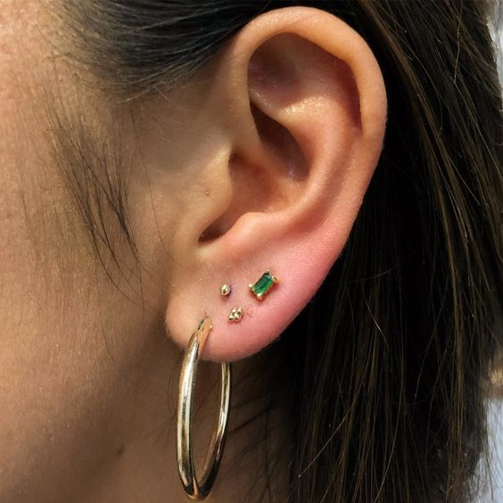 stacked lobe piercings with gold and emerald studs and a gold hoop earring for a bold and chic look