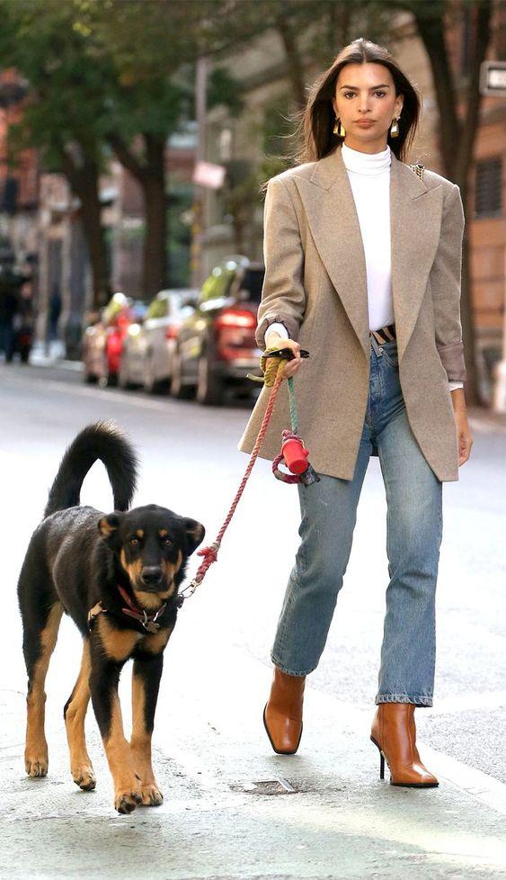 Emily Ratajkowski wearing a white turtleneck, blue jeans, an oversized tan blazer, amber heeled boots is amazing