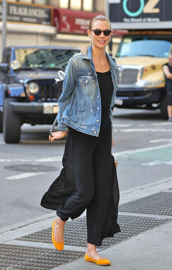 a black jumpsuit with wideleg pants, a blue oversized denim jacket, yellow ballt flats for a chic yet casual look