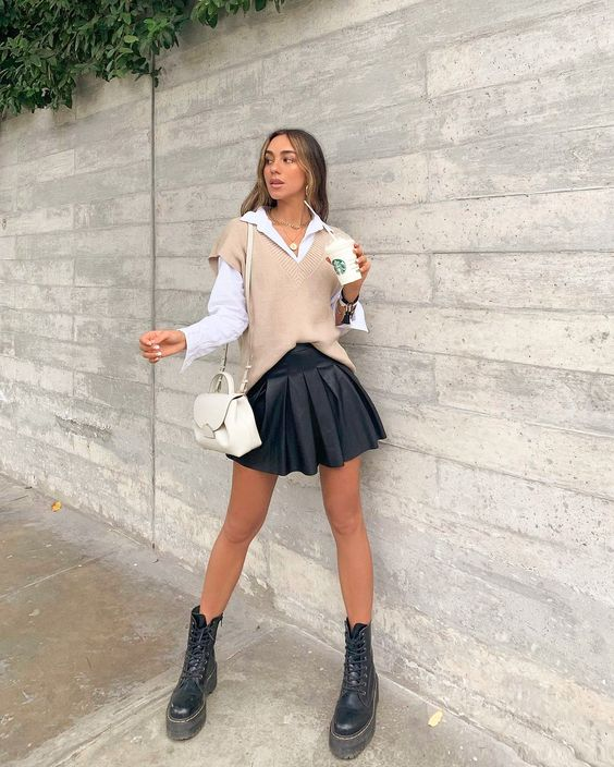a white shirt, a black pleated mini, a tan oversized knit vest, black combat boots and a neutral mini bag