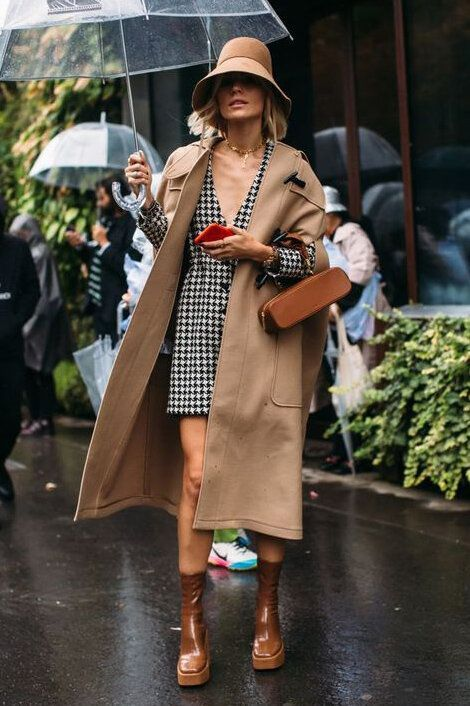 a printed black and white blazer dress, brown chunky boots, a tan trench, a brown bag and a tan bucket hat