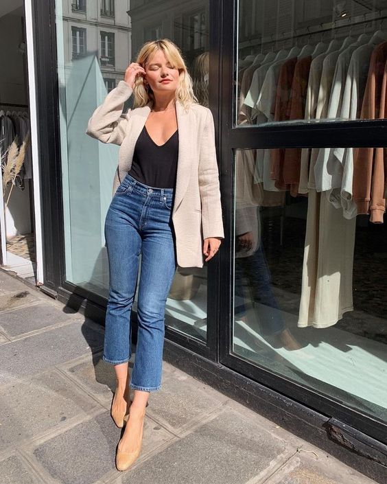 a stylish and simple look with a black top, blue cropped jeans, tan ballet flats, a neutral oversized blazer