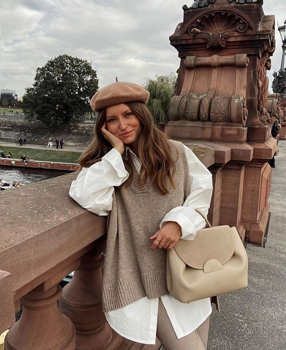 a white oversized shirt, a greige knit vest, tan pants, a creamy bag and a dusty pink beret for the fall
