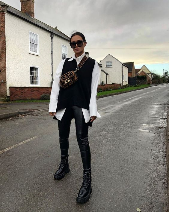 a cool fall outfit with a white shirt, a black knit vest, black leather pants, black combat boots and a printed waist bag