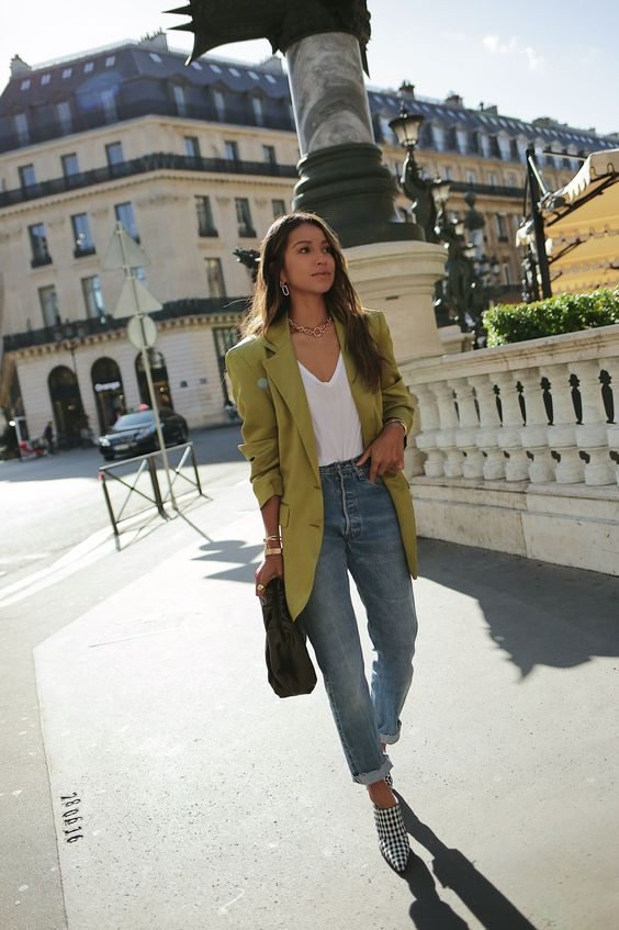 blue jeans, checked booties, a white top, an oversized neon green blazer and a black bag for a trendy look