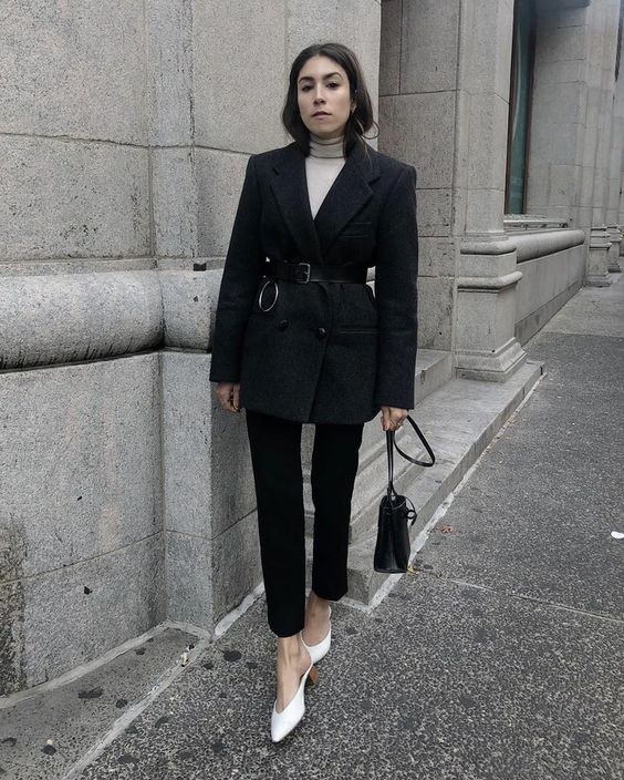a dark fall look with a white turtleneck, black cropped jeans, a navy oversized blazer with a belt, a black bag and white heels