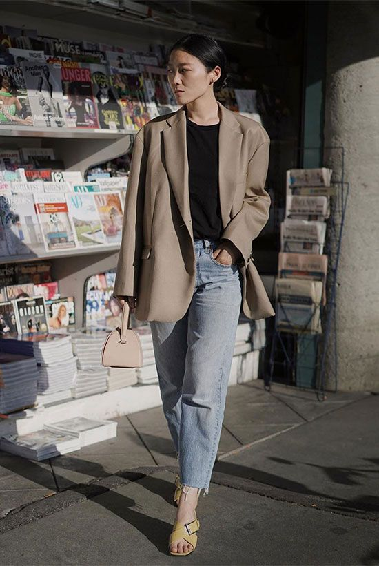 a minimalist outfit with blue jeans, a black t-shirt, a tan oversized blazer, yellow criss cross shoes and a blush bag